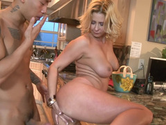 A blonde milf is getting her pussy spread open in the kitchen