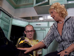 A blonde mature woman removes her clothes and fucks in the kitchen