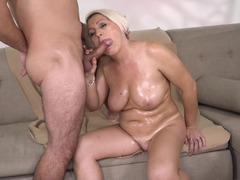 Oiled up blonde granny copulates with young beau on couch