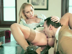 A blonde with a sexy pair of tits is licked on the desk in office